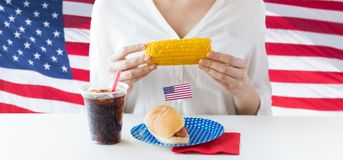 Woman hands holding corn with hot dog and cola. American independence day, celebration, patriotism and holidays concept - close up of woman hands holding corn Royalty Free Stock Photography