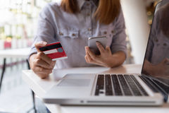 woman hands holding credit card and using mobile smart phone for Stock Photo
