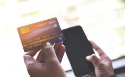 Woman hands holding credit card and using smartphone for online shopping - people paying technology money wallet online payment at. Woman hands holding credit stock photo