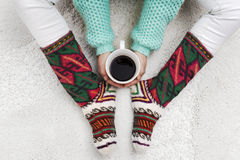 Woman hands holding cup of coffee next to her feet with socks on. A white carpet, top view Royalty Free Stock Photography
