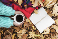 Woman hands holding cup of coffee over leaves background. Stock Images