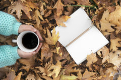 Woman hands holding cup of coffee over leaves background. Top view Royalty Free Stock Image