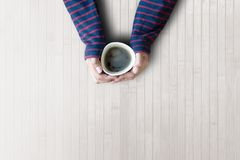 Woman is hands holding cup with coffee, top view, copy space Stock Image