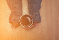 Woman hands holding cup of hot drink on wooden table Royalty Free Stock Photos