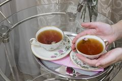 Woman hands holding a cup of hot tea. Woman hands holding one of two cups with hot tea, glass table stock photos