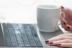 Woman hands holding cup on laptop keyboard stock photo