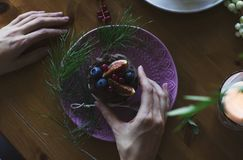 Woman hands holding Cupcake with fig and berries on Christmas ta. Ble Royalty Free Stock Photography