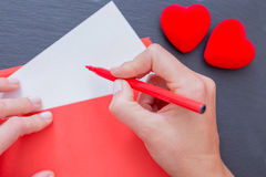Woman hands holding envelope and red felt pen Stock Photo