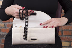 Woman hands holding fancy clutch with black pearl Royalty Free Stock Photography