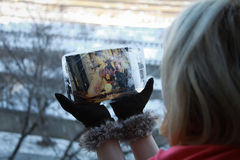 Woman hands holding a frozen weeding photo, brown suede gloves Stock Photo
