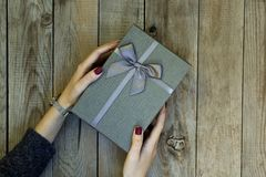 Woman hands holding a gift box on wooden table. royalty free stock photography