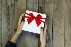 Woman hands holding a gift box on wooden table. royalty free stock photos