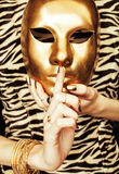 Woman hands holding golden carnival mask, rich. Luxury manicure and jewelry close up on zebra print Stock Image