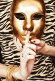 Woman hands holding golden carnival mask, rich luxury manicure and jewelry close up on zebra print, gold everythere royalty free stock images