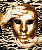 Woman hands holding golden carnival mask, rich luxury manicure and jewelry close up on zebra print Stock Images
