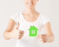 Woman hands holding green house. Showing thumbs up Royalty Free Stock Images
