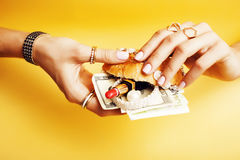 Woman hands holding hamburger with money, jewelry, cosmetic, social issue wealth concept. Close up Stock Photography