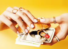 Woman hands holding hamburger with money, jewelry, cosmetic, social issue wealth concept. Close up Stock Images