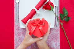 Woman hands holding heart-shaped present box Stock Photography