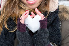 Woman hands holding heart shaped snowball Royalty Free Stock Photography