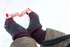 Woman hands holding heart shaped snowball royalty free stock images