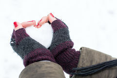 Woman hands holding heart shaped snowball stock photography