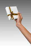 Woman Hands holding Holiday Present White Box with Yellow Golden Ribbon Stock Image