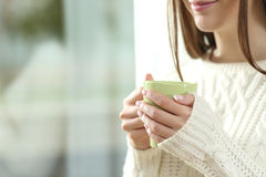 Woman hands holding a hot coffee cup in winter. Close up of a woman hands holding a hot coffee cup in winter near a window at home with outdoors in the Stock Photo