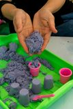 Woman hands holding kinetic sand and letting go into mini plasti Stock Photos