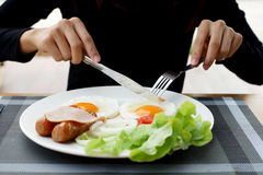 Woman hands holding knife and fork during eating breakfast. Closeup of woman hands holding knife and fork during eating breakfast stock photo