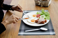 Woman hands holding knife and fork during eating breakfast royalty free stock photography