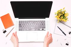 Woman hands holding laptop workspace with diary flowers. Woman hands holding laptop. Workspace with diary and flowers on the white background. Flat lay, top view royalty free stock photography