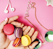 Woman hands holding macaroons with lot of girl stuff on pink background, girls accessories concept Royalty Free Stock Photo