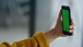 Woman hands holding mobile phone with greenscreen. Girl posing for selfie
