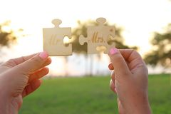 Woman hands holding Mr and Mrs sign during sunset time. harmony and wedding concept. royalty free stock photography