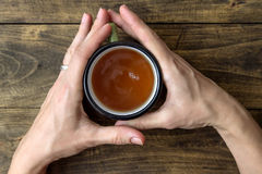 Woman hands holding mug of hot drink that standing on wooden tab Stock Photos
