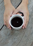 Woman hands holding mug of hot drink. That standing on wooden table Royalty Free Stock Photo