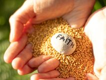 Woman hands holding mustard seeds and rock with the handwritten word faith