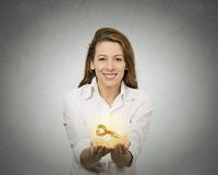 Woman hands holding offering new key. Portrait happy woman, hands holding offering new golden key to success isolated grey wall background. Positive human royalty free stock photography