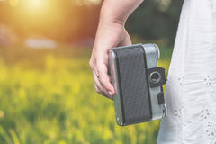 Woman hands are holding old vintage film camera outdoors. Toned. Woman hands are holding old vintage film camera outdoors. Toned Royalty Free Stock Image