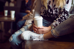 Woman hands holding paper coffee cup while sitting in coffee shop Royalty Free Stock Photography