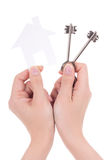 Woman hands holding paper house and keys isolated on white. Background Royalty Free Stock Photo