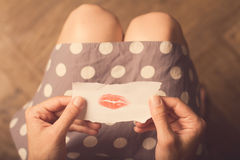Woman hands holding a paper note with lipstick traces Royalty Free Stock Photography