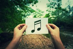 Holding music note. Woman hands holding a paper sheet with music note inside, in the middle of the nature with a river flowing near the forest. Listening to the Stock Photo