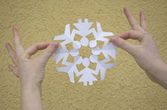 WOMAN HANDS HOLDING PAPER SNOWFLAKE CUT AS PEOPLE IN CIRCLE Stock Image