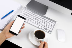 Woman hands holding the phone with isolated screen and cup of coffee. Business workplace with keyboard and business objects Royalty Free Stock Photo