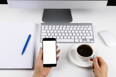 Woman hands holding the phone with isolated screen and cup of coffee. Business workplace with keyboard and business objects Royalty Free Stock Image