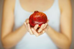 Woman hands holding a pomegranate, sensual studio shot Royalty Free Stock Images