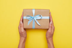 Woman hands holding present with box decorated with blue ribbon Stock Photography