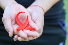Woman hands holding red AIDS awareness ribbon. Aids Awareness campaign royalty free stock photography